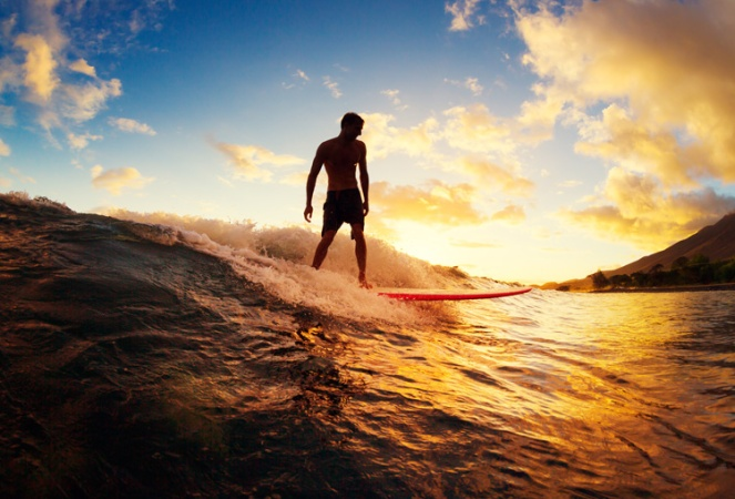 Surfing at Sunset. Young Man Riding Wave at Sunset. Outdoor Acti